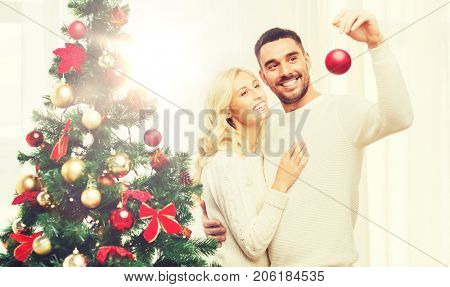 family, x-mas, winter holidays and people concept - happy couple decorating christmas tree with ball at home