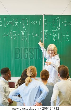 Woman as math teacher in school explains formula to students