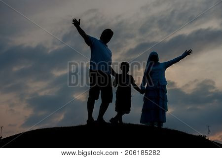 silhoutte of happy family enjoying themself on cliff
