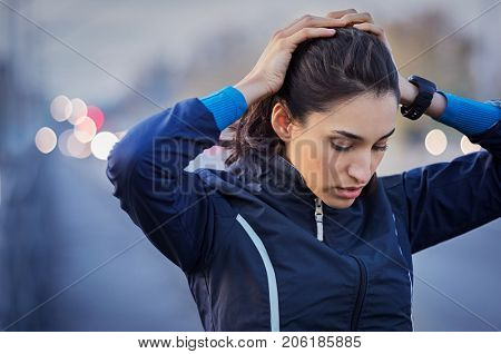 Young runner taking a break from jogging while holding head and breathing outdoor. Sporty girl resting after a long run early in winter morning. Young athletic woman with urban background at sunset.