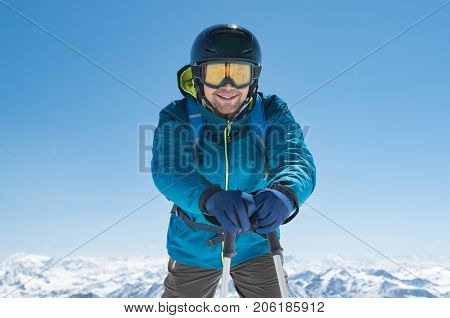 Happy man holding ski poles standing on snow mountain and looking at camera. Mountaineer skier enjoying winter holiday with snowy mountains in background. Smiling guy wearing ski mask and helmet.