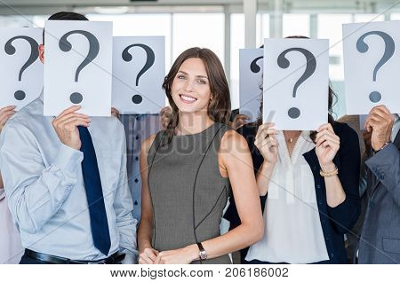Businesswoman standing out of the crowd. Happy smiling business woman with other people hiding their faces behind a question mark sign. Successful businesswoman find her job and career path.
