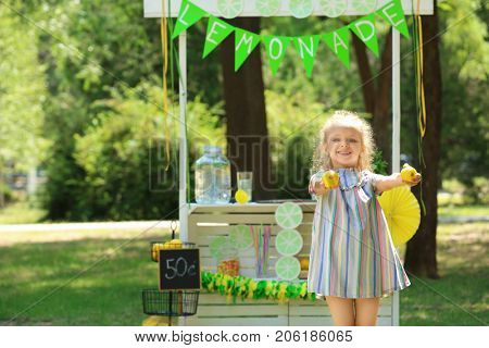 Cute smiling girl with lemons near lemonade stand in park