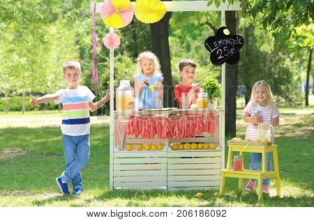 Happy children making lemonade at stand in park