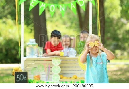 Funny little girl near lemonade stand in park