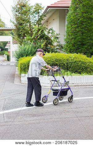 TOKYO JAPAN - SEPTEMBER 16 : unidentified asian old leprosy man walking with wheel waker for exercising in Tama Zensho Hospital on September 16 2017 in Tokyo Japan.