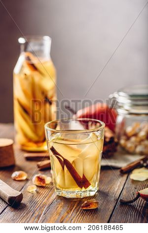 Infused Water in Glass and Bottle with Sliced Pear Cinnamon Stick Ginger Root and Some Sugar. Ingredients on Wooden Table. Vertical Orientation.