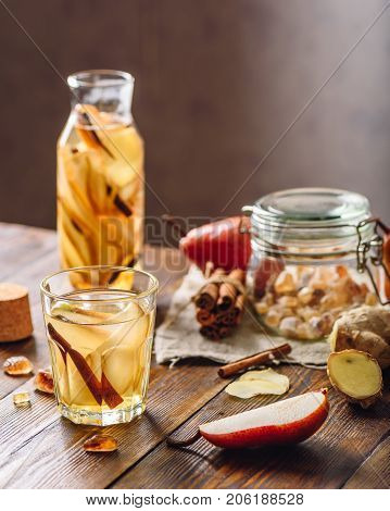 Detox Water Infused with Sliced Pear Cinnamon Stick Ginger Root and Some Sugar. Ingredients on Wooden Table. Vertical Orientation.