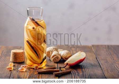Bottle of Water with Sliced Pear Cinnamon Stick Ginger Root and Dark Sugar. Copy Space.