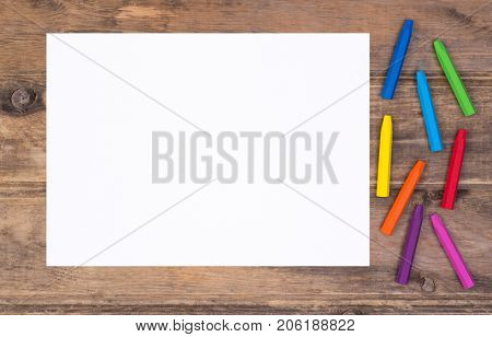 Blank piece of paper with colorful crayons on  kid's desk, top view with copy space