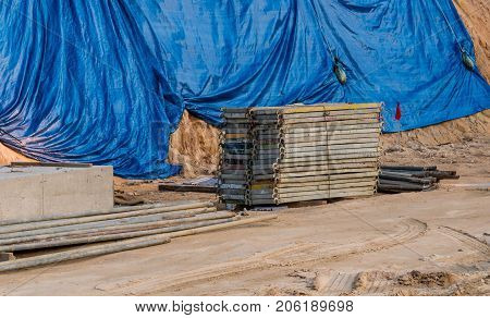 Building materials at a construction site with a blue tarp covering a hillside in the background