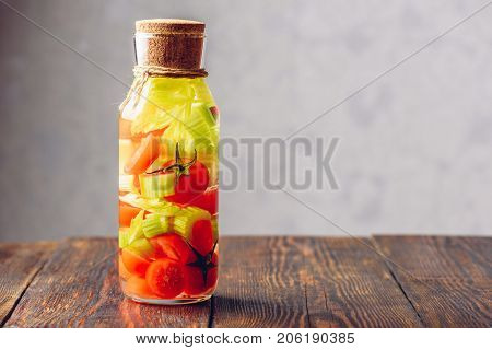 Bottle of Water Infused with Cherry Tomato and Celery Stems. Copy Space on the Right.
