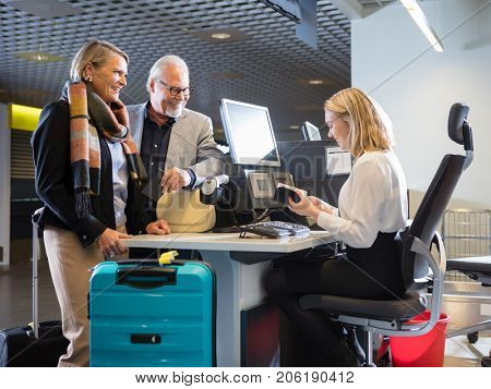 Business Couple Looking At Staff Checking Passport At Airport Ch