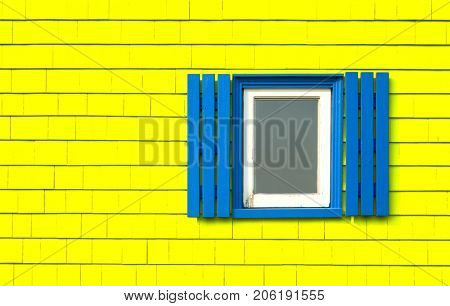 Traditional window with blue shutters on a bright yellow wooden tiles wall in Iles de la Madeleine in Quebec, Canada