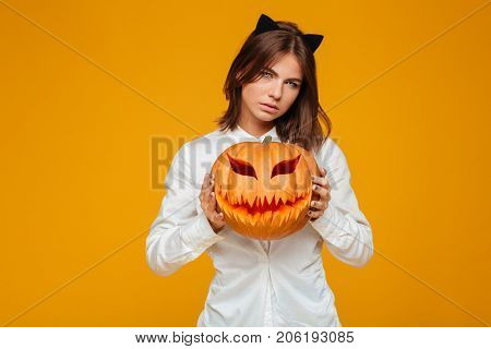 Image of serious young woman dressed in crazy cat halloween costume over yellow background with pumpkin.
