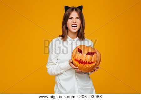 Picture of emotional young woman dressed in crazy cat halloween costume over yellow background with pumpkin.