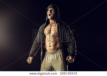 Athlete man bodybuilder strains all muscles and screams. Black background. Achievements in sports.