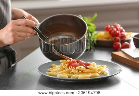Woman adding tasty tomato sauce to pasta on plate