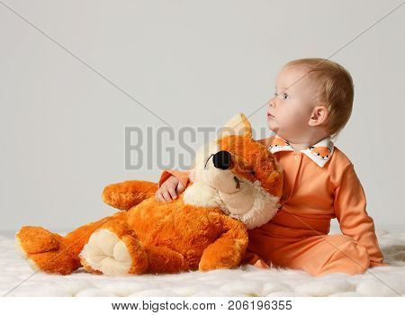 Infant child baby kid toddler sitting with soft fox toy and looking at the corner on a gray background