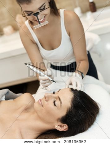 Cosmetician working, making permanent makeup in beauty parlour.
