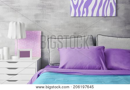 Lilac accent in modern interior. Comfortable bed with pillows in room