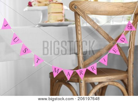 Garland with text JUST MARRIED on chairs. Concept of lesbian wedding
