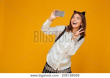 Young teenage schoolgirl in uniform with backpack taking a selfie while standing and showing peace gesture isolated over orange background