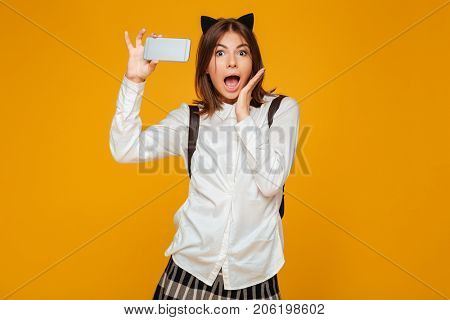 Shocked young teenage schoolgirl in uniform with backpack taking a selfie while standing isolated over orange background