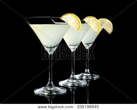 Glasses of lemon drop martini with slices of fruit on black background