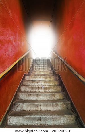 Old grungy stairs with handrails on red wall with light on top