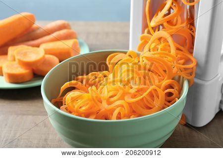 Spiral vegetable slicer with carrot spaghetti on table
