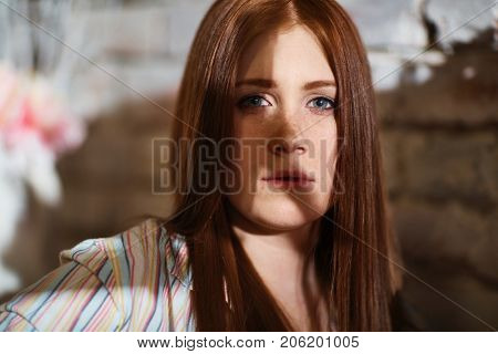 Closeup portrait of young ginger-haired woman, looking at camera.