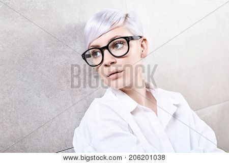 Closeup portrait of young woman in glasses, daydreaming.