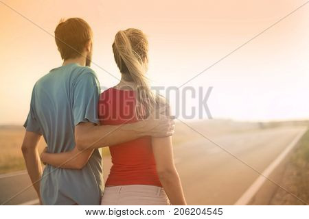 Couple of young lovers hugging each other while looking at the sunset on a long solitary road