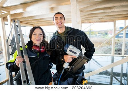Male And Female Carpenters With Tools Standing At Site
