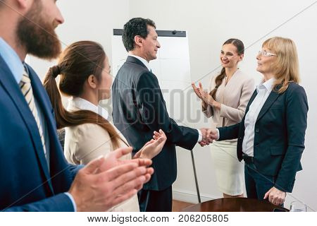 Two middle-aged business associates smiling while shaking hands as agreement after meeting in the conference room of a multinational company