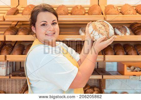 Saleslady in bakery shop presenting bread to potential buyer