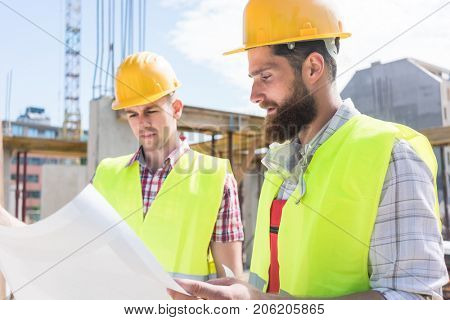 Two young construction workers wearing yellow hard hats and reflective safety vests while analyzing together the plan of a new building