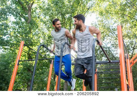Low-angle view of two handsome young men passionate about fitness doing dips exercise for triceps in a calisthenics park with modern equipment