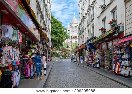 PARIS,FRANCE - AUGUST 4,2017 : Street scene with souvenir shops in Montmartre with the Sacre Coeur Basilica in the background