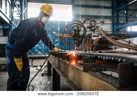 Asian worker wearing protective equipment while using CNC plasma cutter