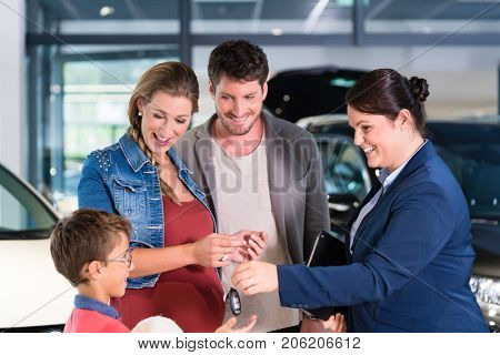 Car dealer giving key to new auto to family, mother is pregnant