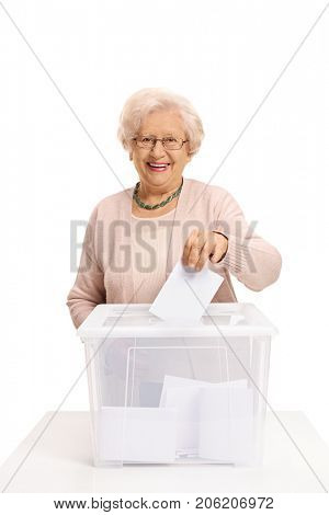 Elderly woman casting a vote into a ballot box and smiling isolated on white background