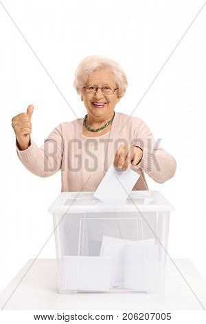 Elderly woman voting and making a thumb up sign isolated on white background