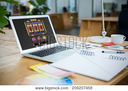 Slot machine on mobile screen against laptop and color swatch on table