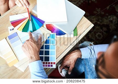 Overview of designers hands during discussion and choosing color for interior
