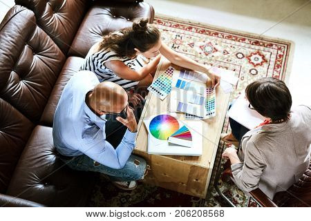 Top view of three designers discussing color palettes at start-up meeting