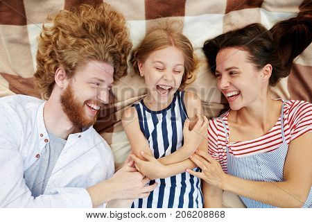 Playful parents tickling their daughter and laughing altogether