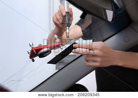 Specialist fixing crack on car windshield in repair shop poster