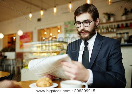 Well-dressed businessman in eyeglasses reading latest news by breakfast in cafe